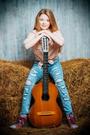 in jeans: Adolescente chica hermosa en camisa y pantalones vaqueros rasgados tocando la guitarra sentado en el heno. Jeans de moda. Estilo occidental.