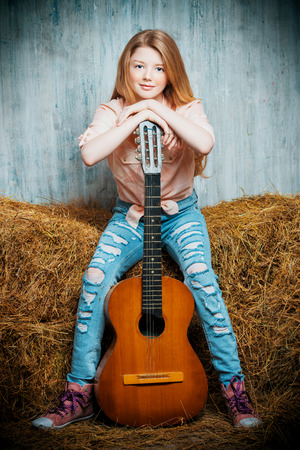 torn jeans: Beautiful girl teenager in shirt and torn jeans playing guitar sitting on hay. Jeans fashion. Western style.