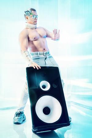 futuristic man: Futuristic muscular man dancing with huge music speakers on a luminous transparent background. Music, technology. Futuristic DJ. Stock Photo