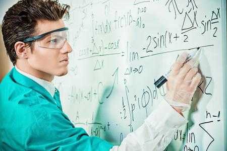 teorema: Un joven científico la realización de investigaciones, haciendo experimentos y escribe los resultados. Foto de archivo