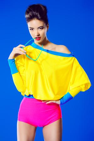 Attractive fashion model posing in vivid colourful clothes. Bright fashion. Summer style. Studio shot. Stock Photo