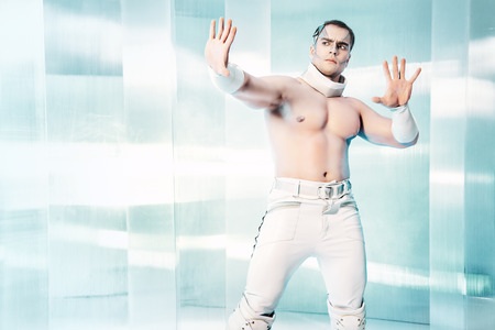 luminous: Technologies of the future, man of the future. Handsome muscular man with futuristic make-up stands on a luminous transparent background and touches something virtual. Stock Photo