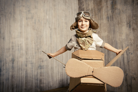airman: Cute dreamer boy playing with a cardboard airplane. Childhood. Fantasy, imagination. Retro style. Stock Photo