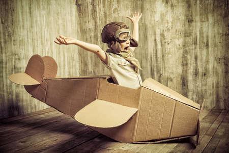 piloto: Lindo chico soñador jugando con un avión de cartón. Niñez. Fantasía, imaginación. Estilo retro.