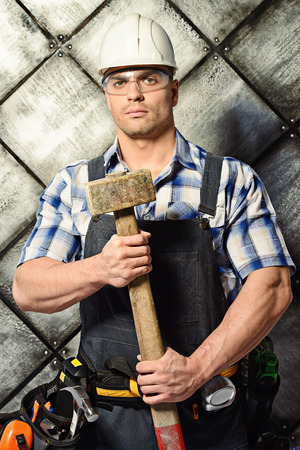 erector: Handsome construction worker wearing uniform and tools over grunge industrial . Job, occupation. Stock Photo
