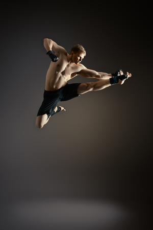arte marcial: El hombre en ropa deportiva que realiza un retroceso. Artes marciales. Estudio de disparo.