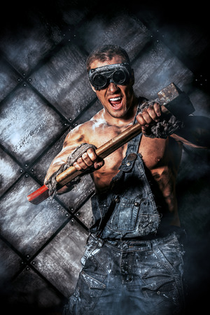 mattock: Muscular dirty coal miner with a pickaxe over dark grunge background. Mining industry. Art concept. Stock Photo