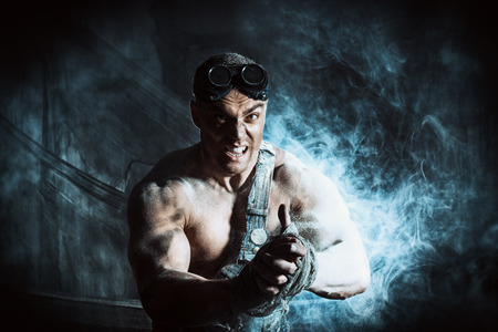 dirty man: Brutal muscular dirty man expressing aggression over dark grunge background. Mining industry. World of the future, Apocalypse. Stock Photo