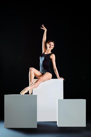 turnanzug: Elegante sch�ne Ballett-T�nzerin in schwarz Ballett-Trikotanzug posiert im Studio auf wei�em W�rfel. Kunstkonzept.