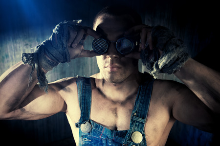 dirty man: Brutal muscular dirty man in goggles over dark grunge background. Mining industry. World of the future, Apocalypse.