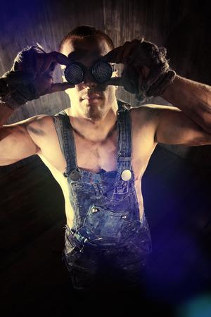 hombre sucio: Hombre sucio musculoso Brutal en anteojos sobre fondo oscuro del grunge. Industria minera. Mundo del futuro, Apocalipsis.