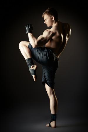 martial: Man in sportswear performing a kick. Martial arts. Studio shot.
