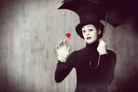Portrait of a male mime artist standing under umbrella expressing sadness and loneliness. Love. Grunge background. photo