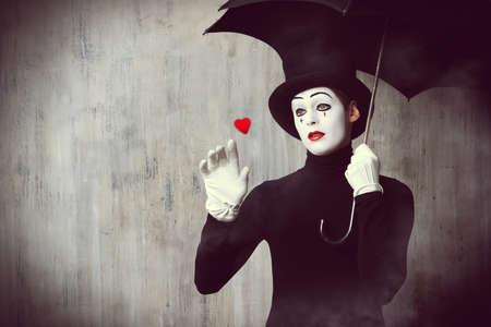 mimo: Retrato de un mimo macho coloca bajo el paraguas que expresan tristeza y soledad. Amor. Grunge fondo.