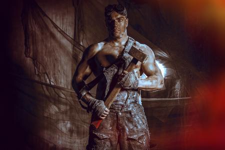 hombre fuerte: Minero de carbón guapo musculoso con un martillo sobre el fondo oscuro del grunge. Industria minera. Concepto del arte.