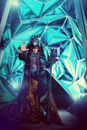 ethnic dress: Portrait of a male shaman in ethnic dress on a background of a futuristic exterior. Fantasy concept, magic.