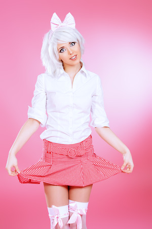 Cute teen girl wearing white wig and school uniform with stockings posing over pink background. Anime style. photo