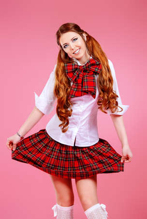 checkered skirt: Cute smiling teen girl in school plaid skirt and white blouse posing over pink background. Anime style.