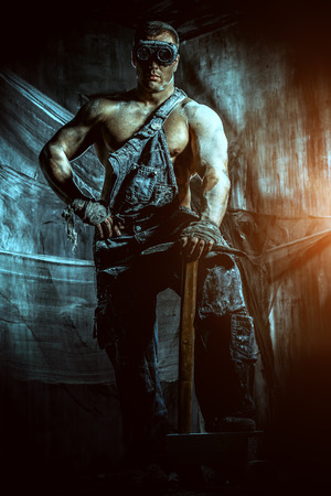coal miner: Masculine dirty coal miner with a pickaxe over dark grunge background. Mining industry. Strength. Bodybuilding.