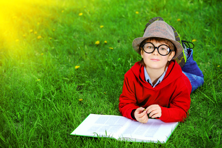 Cute 7 years old boy lying on a grass and reading a book. Summer day. photo