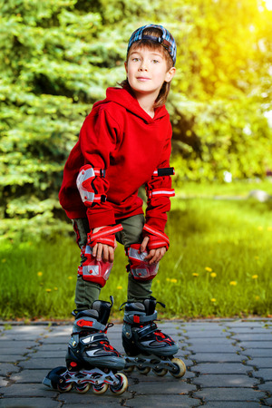 7 year old: Cool 7 year old boy  blades on the street. Childhood. Summertime. Stock Photo