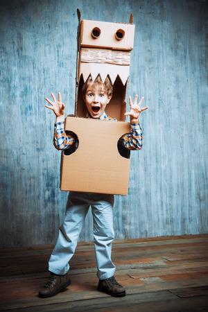 cute dinosaur: Little dreamer boy playing with a cardboard dragon, dinosaur. Childhood. Fantasy, imagination.