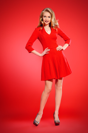 Full length portrait of a charming young woman in red dress and with blonde curled hair. Beauty, fashion. Cosmetics, make-up. Red background. photo