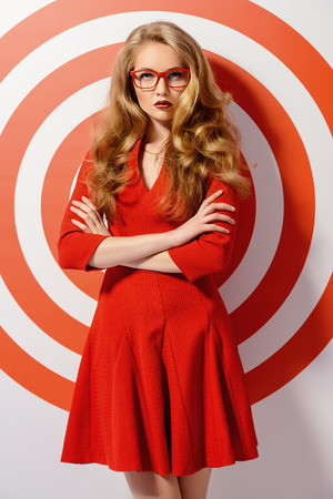 strict: Gorgeous fashion model in red dress and elegant red glasses posing over red circles of the target. Beauty, fashion. Optics, eyewear.