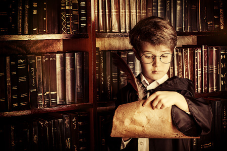 manuscripts: A boy stands in the library by the bookshelves with many old books and holds old manuscripts. Educational concept. Science. Vintage style. Stock Photo