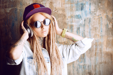 modern generation: Trendy teenage girl with blonde dreadlocks listening to music on headphones. Jeans style. Modern generation. Stock Photo