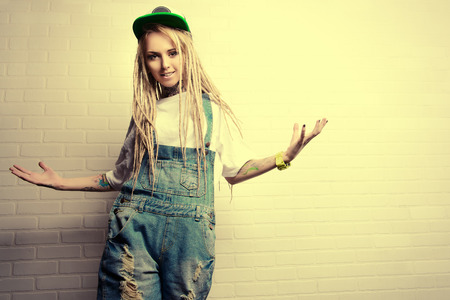 naughty girl: Modern teenage girl with blonde dreadlocks standing by the brick wall. Jeans style. Modern generation.