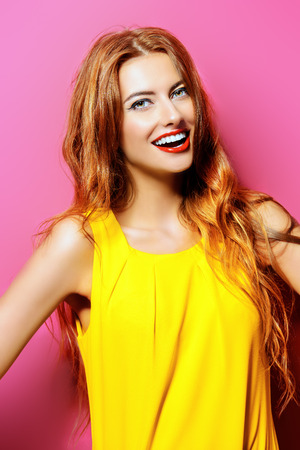 sincerely: Happy emotional young woman in bright yellow dress laughing sincerely. Beauty, fashion concept. Hair, healthy hair. Stock Photo