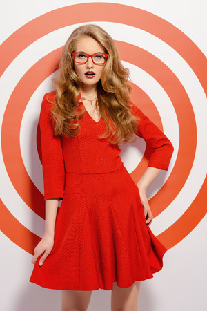 gorgeous businesswoman: Gorgeous fashion model in red dress and elegant red glasses posing over red circles of the target. Beauty, fashion. Optics, eyewear.