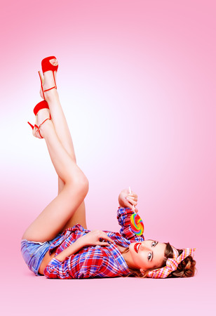 sexy lollipop: Sexy pin-up girl in shorts and high heels lying on a floor with bright lollipop over pink background. Beauty, fashion. Full length portrait.