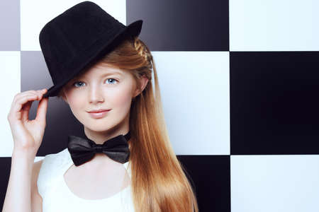 pretty teen girl: Elegant teen girl wearing white dress, black hat and a bow-tie posing on a background of black and white squares. Youth fashion. Stock Photo