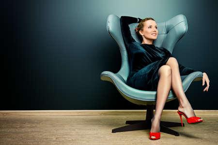 lifestyle: Porträt einer atemberaubenden modischen Modell sitzt auf einem Stuhl im Art Nouveau Stil. Business, elegante Geschäftsfrau. Interior, Möbel.