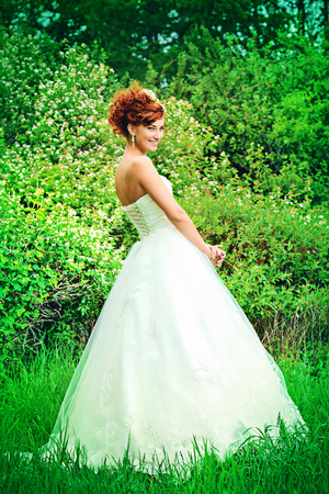 Lovely elegant red-haired bride stands on the lawn. Wedding dress and accessories. photo