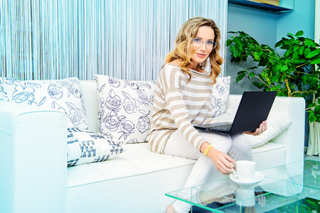 homey: Smiling elegant woman sitting on a sofa with her laptop computer. Home interior, furniture. Lifestyle. Stock Photo