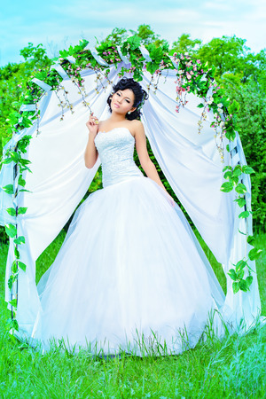 asian bride: Beautiful elegant asian bride stands under the wedding arch. Wedding dress and accessories. Wedding decoration.