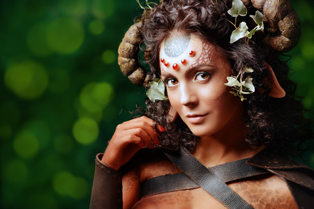 Close-up portrait of a fairy female Faun. Myth and fantasy. Body painting project. Studio shot.