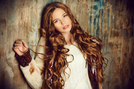 knitwear: Fashion shot of a pretty teenager girl with beautiful long curly hair wearing fur coat. Beauty, fashion.