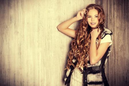 plan éloigné: Mode prise de vue d'une jolie fille adolescente avec une belle longs cheveux bouclés vêtu de la robe tricot blanc et veste de fourrure. Beauté, mode. Banque d'images