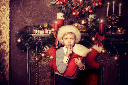 one family: Cute seven year old boy stands with gifts by the fireplace at home. The magic of Christmas. Stock Photo
