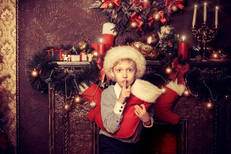 m�gica: Lindo ni�o de siete a�os de edad, se encuentra con regalos por la chimenea en casa. La magia de la Navidad. Foto de archivo
