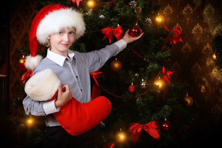 seven year old: Cute seven year old boy stands with gifts by the fireplace at home. The magic of Christmas. Stock Photo