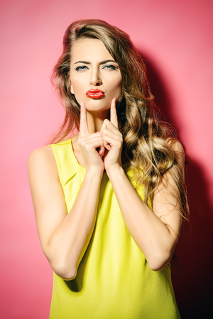 lipstick kiss: Beautiful fashion model in bright yellow dress posing with her long hair. Beauty, fashion concept. Hair, healthy hair.