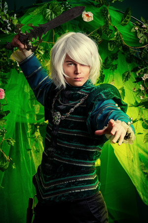 anime young: Noble blond elf with a sword in his hand in the magic forest. Fantasy. Anime style. Stock Photo