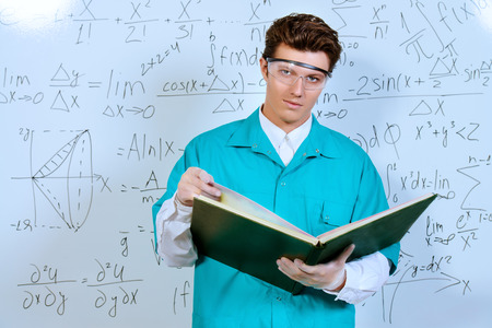 theorem: Young scientist conducting research, making experiments and writes the results. Stock Photo