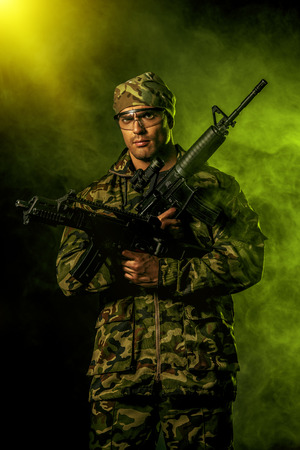 brawny: Brave soldier in camouflage holding automatic rifle. Military. Stock Photo