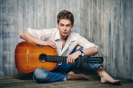 sexy guitar: Romantic young man playing an acoustic guitar, sitting on the wooden floor